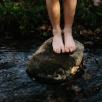 A person earthing / grounding by standing with bare feet standing on a rock in a stream