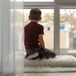 boy looking out window of doctor's office