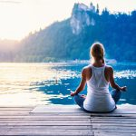 Meditation: A woman meditating by the water