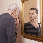 An elderly man looking at his younger self in a mirror