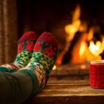 Feet in socks by a fire