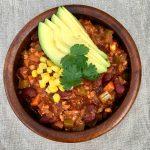 A bowl of vegan chili with sliced avocado