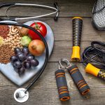 Vegetarian food on a heart-shaped plate with a stethoscope and workout equipment